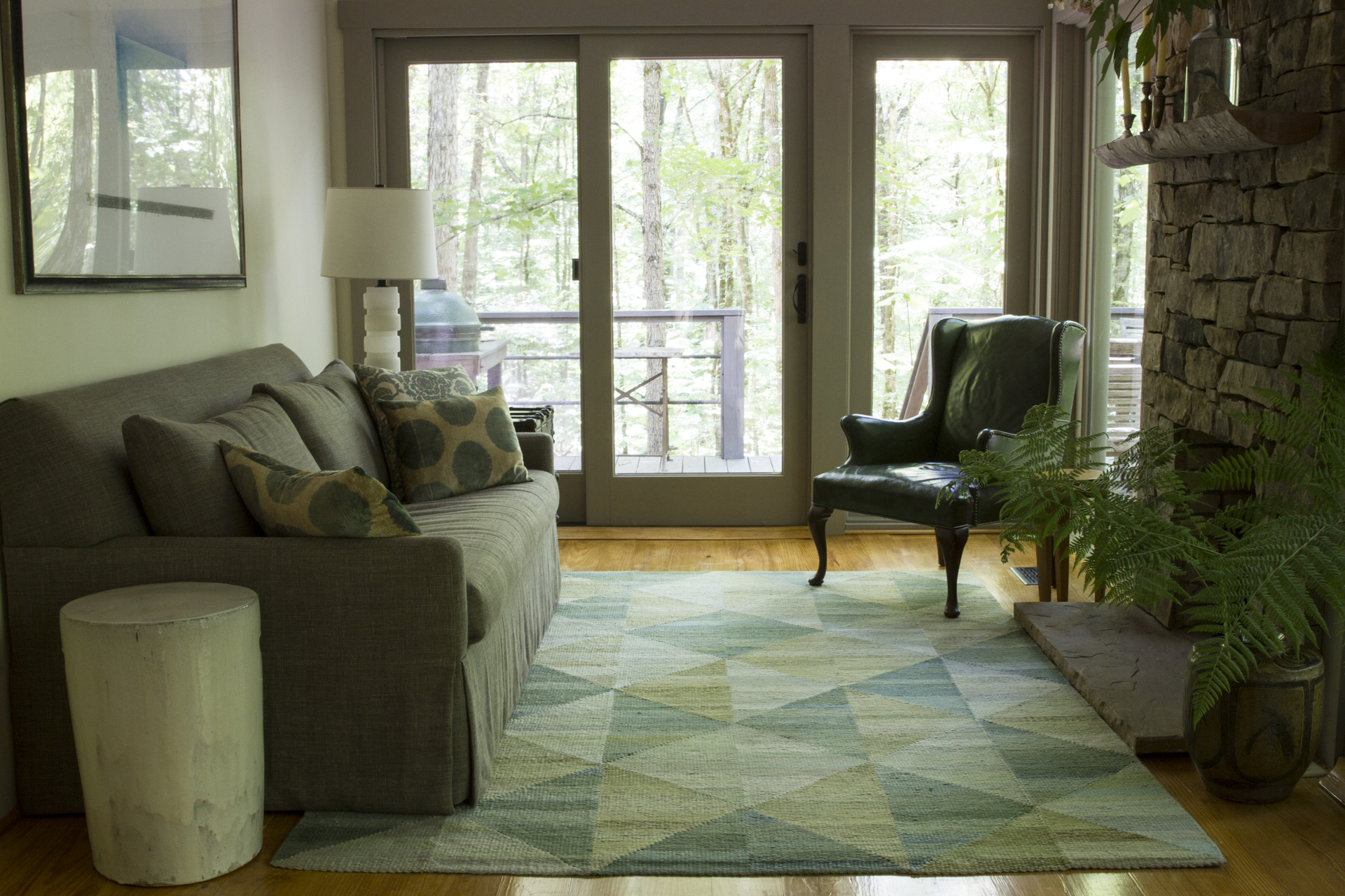 An example of Lyn Sterling Montagne handwoven rugs, in shades of green complements the lush view of this Georgia retreat's relaxed, organic sunroom.